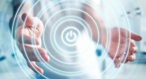 L'uomo d'affari che tiene 3D rende il bottone di potere con la sua mano Immagine Stock
