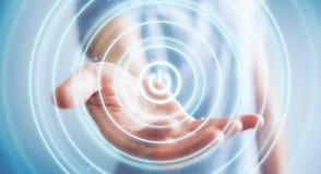 L'uomo d'affari che tiene 3D rende il bottone di potere con la sua mano Fotografie Stock