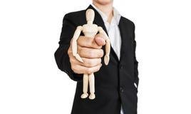 L'uomo d'affari che tiene la figura di legno, concetto di prende il controllo, opprime ed ecc , isolato su fondo bianco immagini stock libere da diritti