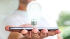 L'uomo d'affari che tiene la lampadina brillante sul telefono cellulare '3D rende Fotografie Stock Libere da Diritti
