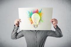 L'uomo d'affari che tiene un cartone con pittura spruzza e lightbul Fotografia Stock Libera da Diritti