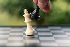 L'uomo d'affari che tiene un re Chess è disposto su una scacchiera usando fotografia stock