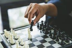 L'uomo d'affari che tiene un re Chess è disposto su una scacchiera usando come il concetto di affari del fondo e concetto di stra fotografia stock