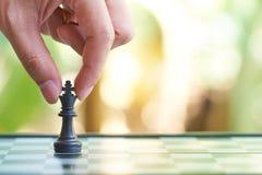 L'uomo d'affari che tiene un re Chess è disposto su una scacchiera usando come il concetto di affari del fondo e concetto di stra fotografie stock libere da diritti