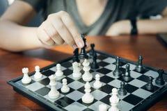 L'uomo d'affari che tiene un re Chess è disposto su una scacchiera usando come il concetto di affari del fondo e concetto di stra fotografia stock libera da diritti