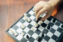 L'uomo d'affari che tiene un re Chess è disposto su una scacchiera usando come il concetto di affari del fondo e concetto di stra immagine stock