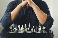 L'uomo d'affari che tiene un re Chess è disposto su una scacchiera usando come il concetto di affari del fondo e concetto di stra immagini stock