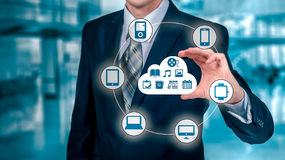 L'uomo d'affari che tocca una nuvola si è collegato a molti oggetti su uno schermo virtuale, concetto circa Internet delle cose Immagine Stock