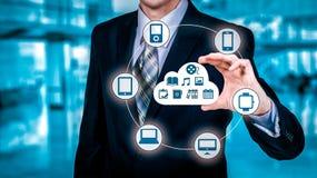 L'uomo d'affari che tocca una nuvola si è collegato a molti oggetti su uno schermo virtuale, concetto circa Internet delle cose Immagini Stock