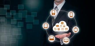 L'uomo d'affari che tocca una nuvola si è collegato a molti oggetti su uno schermo virtuale, concetto circa Internet delle cose Fotografie Stock Libere da Diritti