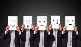 L'uomo d'affari cinque che tiene una carta con le sensibilità differenti di emozione di espressioni facciali del disegno affronta fotografia stock