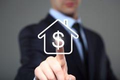 L'uomo d'affari clicca sopra la casetta dell'icona Simbolo di dollaro Lo schermo virtuale Immagini Stock