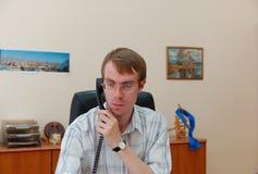 L'uomo d'affari comunica su un telefono Fotografie Stock Libere da Diritti