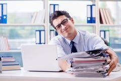 L'uomo d'affari con eccessivo lavoro di ufficio del lavoro che lavora nell'ufficio fotografie stock