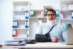 L'uomo d'affari con il braccio rotto che funziona nell'ufficio fotografia stock