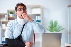 L'uomo d'affari con il braccio rotto che funziona nell'ufficio immagine stock libera da diritti