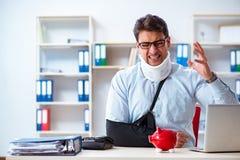 L'uomo d'affari con il braccio rotto che funziona nell'ufficio immagine stock