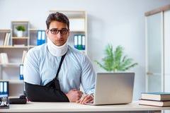 L'uomo d'affari con il braccio rotto che funziona nell'ufficio fotografia stock libera da diritti
