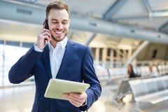 L'uomo d'affari con il PC ed il telefono cellulare della compressa è soddisfatto fotografia stock