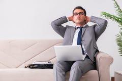 L'uomo d'affari con il taccuino del computer portatile che si siede in sofà Immagini Stock