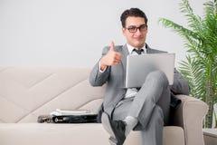 L'uomo d'affari con il taccuino del computer portatile che si siede in sofà Fotografie Stock Libere da Diritti