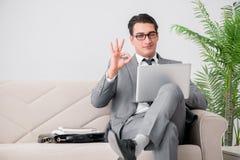 L'uomo d'affari con il taccuino del computer portatile che si siede in sofà Fotografia Stock