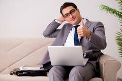 L'uomo d'affari con il taccuino del computer portatile che si siede in sofà Fotografie Stock