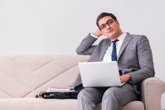 L'uomo d'affari con il taccuino del computer portatile che si siede in sofà Immagine Stock Libera da Diritti