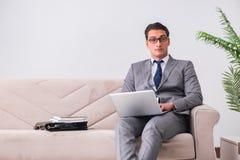 L'uomo d'affari con il taccuino del computer portatile che si siede in sofà Immagini Stock Libere da Diritti