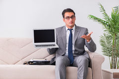 L'uomo d'affari con il taccuino del computer portatile che si siede in sofà Immagine Stock
