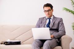 L'uomo d'affari con il taccuino del computer portatile che si siede in sofà Fotografia Stock Libera da Diritti