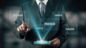 L'uomo d'affari con impara che concetto del mandarino sceglie dalle lingue facendo uso della compressa digitale stock footage