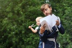 L'uomo d'affari con suo figlio in dell'imbracatura parte posteriore sopra, bambino ha preso la penna e lo SMI Fotografia Stock Libera da Diritti