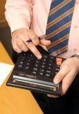 L'uomo d'affari conta i soldi sul calcolatore Fotografia Stock Libera da Diritti