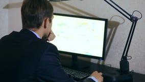 L'uomo d'affari controlla i cambiamenti nel programma sul cambio, esaminante il monitor del computer stock footage