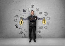 L'uomo d'affari controlla il fondo con le mani dipinte che giudicano le borse dei soldi circondate dai grafici economici e statis Fotografia Stock Libera da Diritti