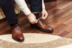 L'uomo d'affari copre le scarpe, uomo che si prepara per il lavoro, mattino dello sposo immagini stock libere da diritti