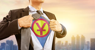 L'uomo d'affari in costume del supereroe con gli yuan cinesi firma e fondo della città Immagine Stock Libera da Diritti