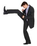 L'uomo d'affari dà dei calci a in su su priorità bassa bianca Fotografia Stock