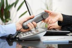 L'uomo d'affari dà il microtelefono della donna lavoro di squadra e servizio clienti fotografie stock