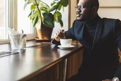 L'uomo d'affari dalla carnagione scura bello giovane beve il caff? in un caff? immagine stock libera da diritti