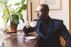 L'uomo d'affari dalla carnagione scura bello giovane beve il caff? in un caff? immagine stock