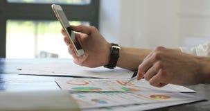 L'uomo d'affari del primo piano delle mani conduce la ricerca ed ottenere a smartphone di dati i piccoli architetti creativi di a archivi video
