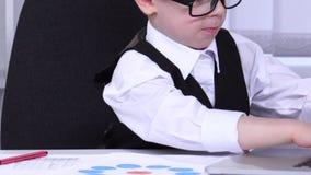 L'uomo d'affari del ragazzino che esaminano i grafici ed i dati sono digitati in un computer portatile archivi video
