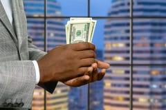 L'uomo d'affari della megalopoli tiene i soldi fotografia stock