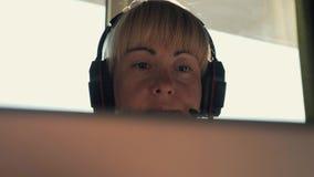 L'uomo d'affari della ragazza in cuffie comunica su Internet nei raggi del sole video d archivio