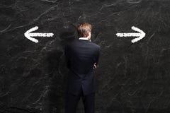 L'uomo d'affari deve decidere fra le due direzioni Fotografia Stock Libera da Diritti