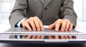 L'uomo d'affari, digitante sul suo computer portatile Fotografie Stock Libere da Diritti