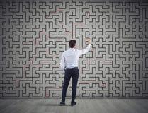 L'uomo d'affari disegna la soluzione di labirinto Concetto di soluzione dei problemi immagine stock
