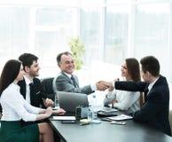 L'uomo d'affari e l'investitore stringono le mani al tavolo delle trattative fotografia stock
